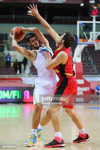 Maxym Korniyenko of Ukraine handles the ball against Sam Van Rossom of Belgium during the FIBA EuroBasket 2015 Group D basketball match between...