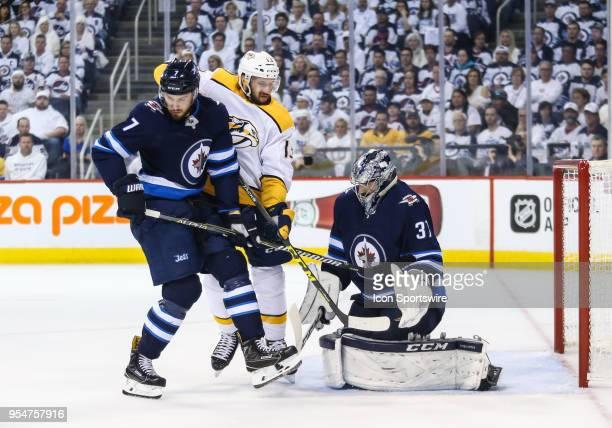 Winnipeg Jets defenseman Ben Chiarot jostles for position with Nashville Predators forward Nick Bonino in front of Winnipeg Jets goalie Connor...