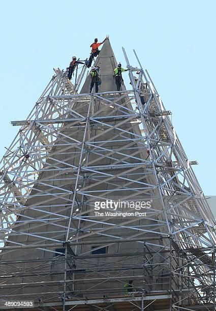 A worker reaches out to grab the top of the Washington Monument to pull himself up as they erect the scaffolding at the top of the 555foot Washington...