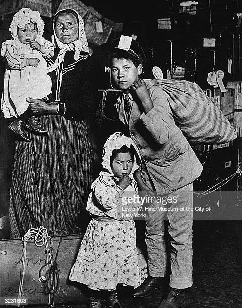 An Italian immigrant woman stands with her three children in front of steamer trunks at the Ellis Island processing center New York City The son...