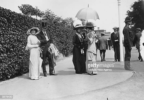Lady Bridget Coke Countess of Airlie stands on the left while her blackclad mother the Countess of Leicester chats to another welldressed lady at...