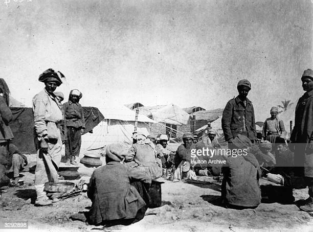 Kurds Arabs and Persians around the cookhouse in a prison camp in Mesopotamia