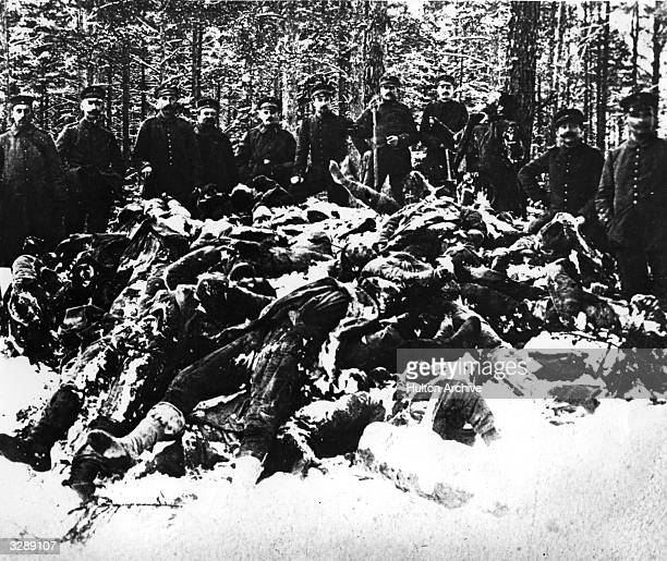 A pile of dead Bolsheviks lie frozen in the snow guarded by German soldiers during the Russian Civil War
