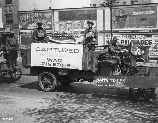 US soldiers stand on a float holding a cage of carrier pigeons and a banner bearing the legend 'Captured German War Pigeons' during a Victory Parade...