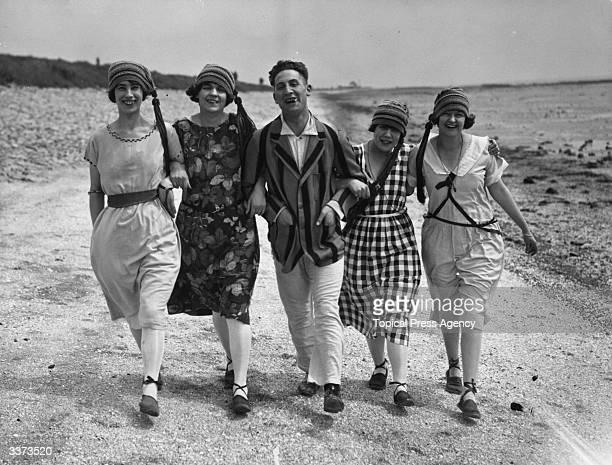 A group of friends enjoying a walk along the beach at Canvey Island in Essex