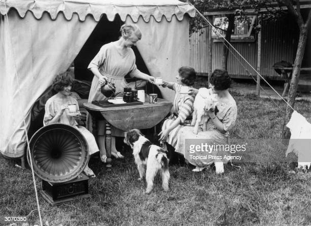 Young ladies enjoying a cup of tea and music when camping on the Chiltern Hills.