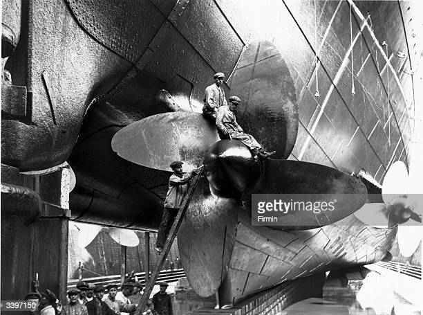 Men at work on the propellers of the merchant ship 'Mauretania' during her refitting in the dry dock at Cherbourg