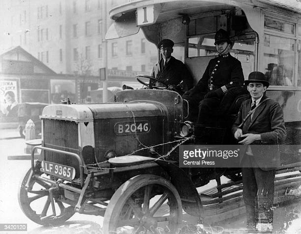 A police officer rides with volunteer bus drivers during the General Strike of 1926 Barbed wire across the bonnet gives added protection against...