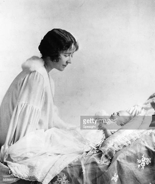 Elizabeth, Duchess of York , looking at her first child, future Queen, Princess Elizabeth.