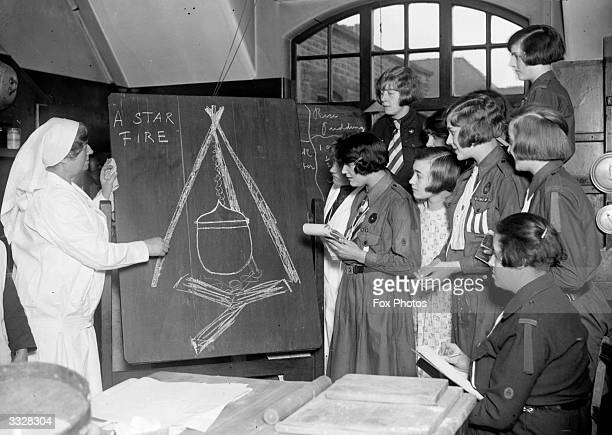 Cookery class for girl guides given by a nurse. A drawing on a blackboard shows how to hang a cooking pot over a log fire.