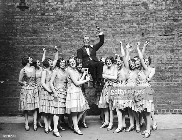 Comedian and comic actor Leslie Henson is chaired by cheering members of the chorus to celebrate ten years at the Winter Garden Theatre