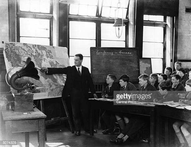 Pupils in a London County Council school using the radio for lessons on the lumber industry, helped by a large map.