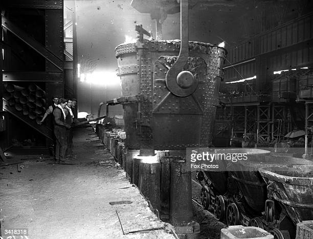 Workmen in a steel mill pouring molten steel into an ingot mould