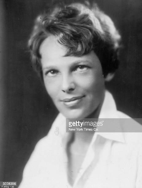Studio headshot portrait of American aviator Amelia Mary Earhart smiling in a white blouse
