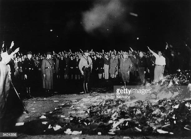 German soldiers and civilians give the Nazi salute as thousands of books smoulder during one of the mass bookburnings implemented throughout the...