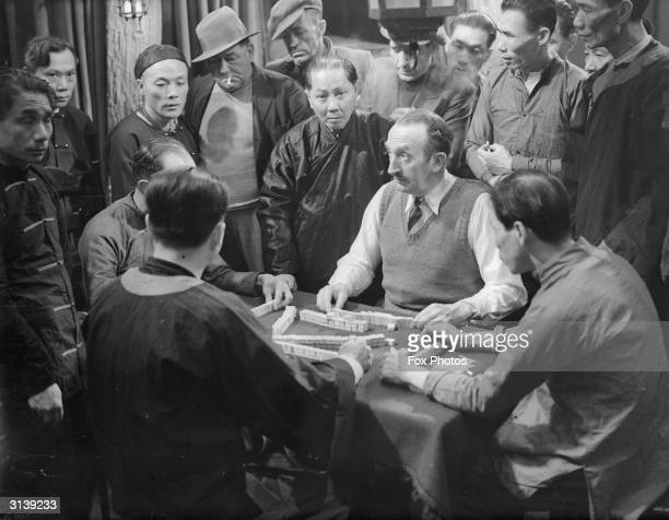 Comic actor Tom Walls playing Mah Jong on a film set with Chinese opponents