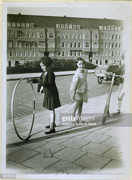 EXCLUSIVE Anne Frank plays with a jump rope as her friend Sanne Ledermann plays with a hoop on a sidewalk in Amsterdam Holland Taken from the photo...