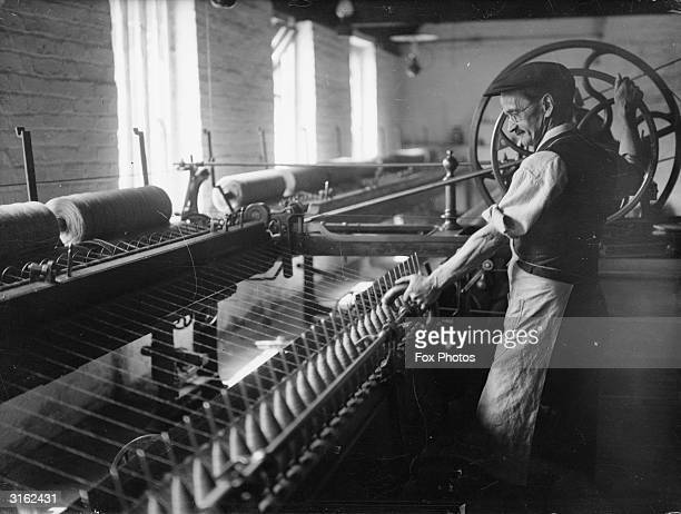 A worker threading yarn at Priory wool factory in Brecon