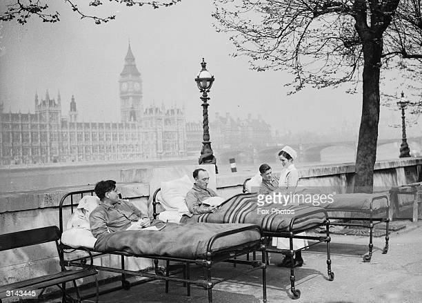 Tuberculosis patients from St. Thomas' Hospital rest in their beds in the open air by the River Thames, opposite the Houses of Parliament.