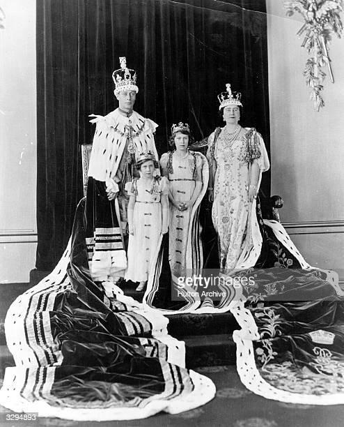 King George VI, and Queen Elizabeth with their daughters, Princesses Elizabeth and Margaret Rose in their coronation robes.