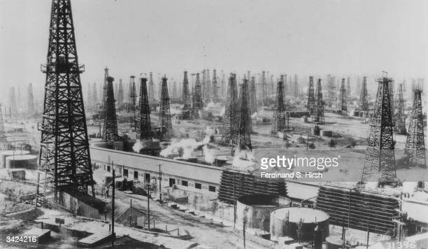 An oilfield of rotary derricks in the USA The building in the foreground is a gasoline extraction plant