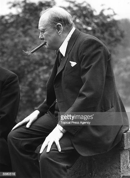 British politician Winston Churchill smoking a cigar at his home in Chartwell Kent
