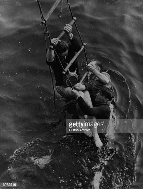 Three men being rescued from the sea after having to abandon ship as they were evacuated from the beaches at Dunkirk They cling to a ladder let down...