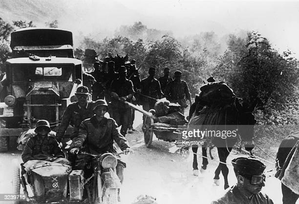German military convoy overtakes a group of Greek peasants on a rural track during the early stages of the German occupation of Greece.