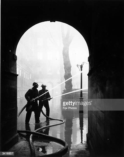 Fire fighters tackle a blaze in London's Temple, home to barristers and lawyers, following an air raid over the city.