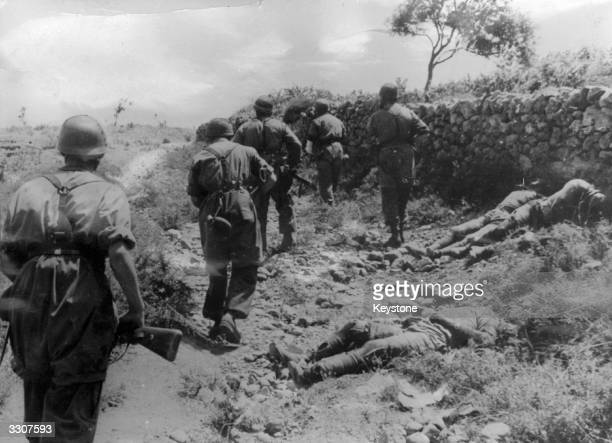 German paratroopers advance during the invasion of Crete On the right are bodies of British soldiers