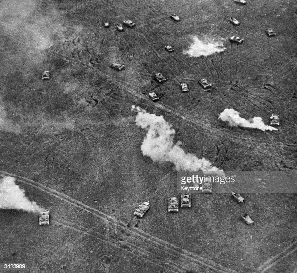 Puffs of smoke issue from Soviet tanks hit by German Stukas during a tank battle in Russia