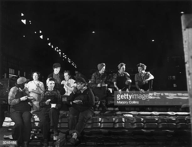 Group of female workers sit on a pile of steel billets, eating their lunches in the processing department of Republic Steel Company, Buffalo, New...