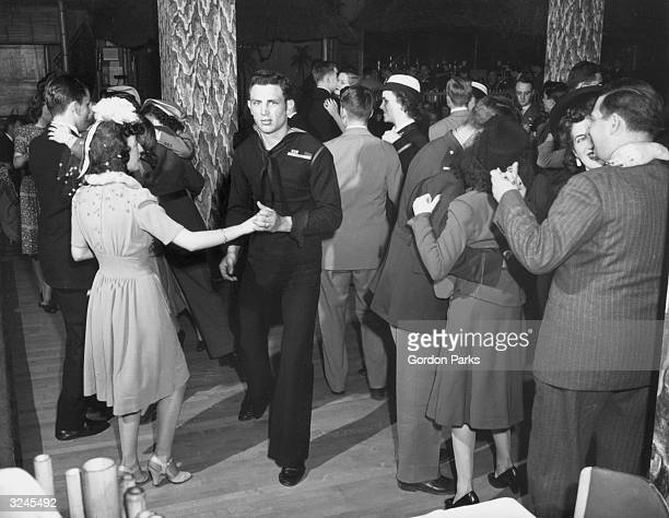 Male and female military personnel dance with their partners on the floor at the Hurricane ballroom, New York City.