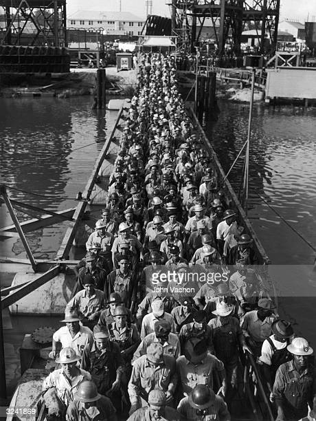 Workers crowd a bridge as they leave a shipyard in Beaumont, Texas, World War II.