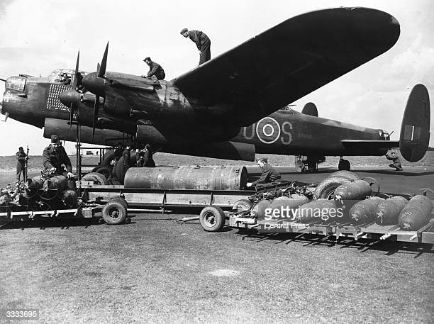 British airmen load bombs onto a Lancaster Bomber plane.