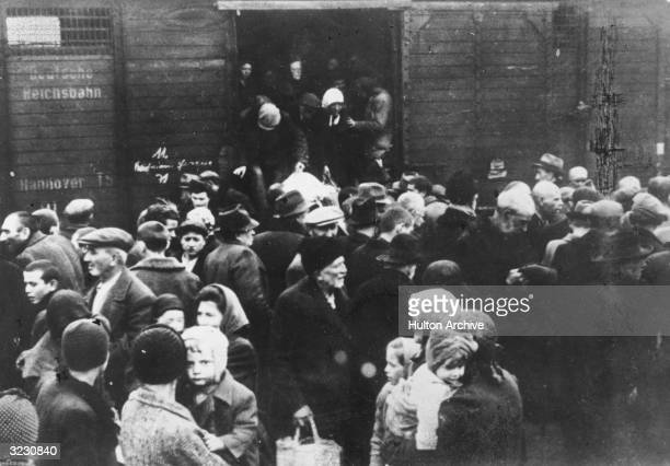 Jews deported from Hungary exit a German boxcar onto a crowded railway platform at Auschwitz concentration camp, Poland.