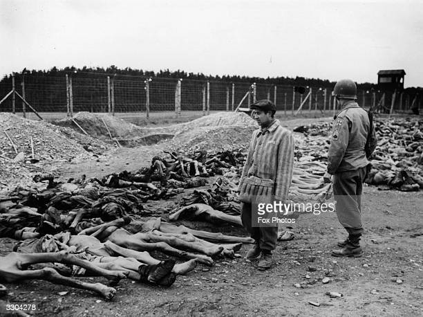 A US soldier and a Polish Jew who had been a prisoner at Lager 3 Concentration Camp looks at bodies of dead inmates