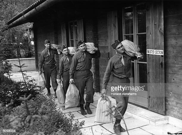 Men of the 101st Airborne Division carry sacks of Heinrich Himmler's loot out of its hiding place in a barn near Berchtesgaden Currency amounting to...