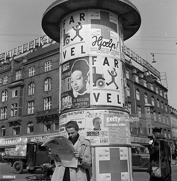 An advertising pillar in the Raadhusplasden the main city square in Copenhagen provides a good leaning post for a city dweller while he scans his...