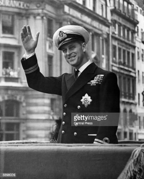 Prince Philip, Duke Of Edinburgh waving through the open roof of a car.
