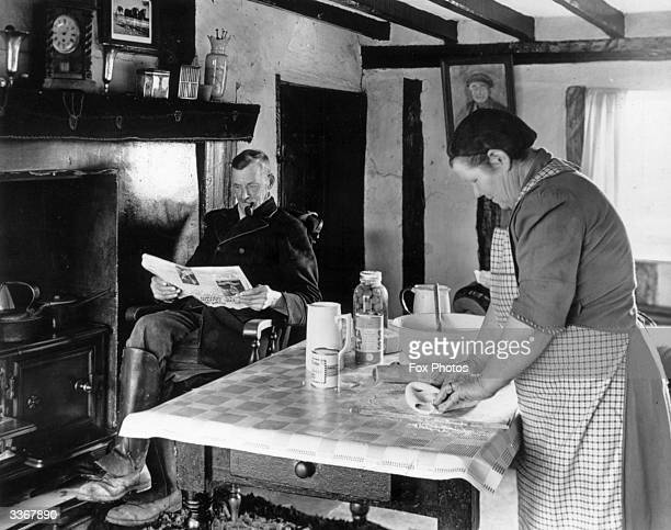 Farmer's wife baking in her 16th century farmhouse kitchen in Essex while her husband is reading the newspaper
