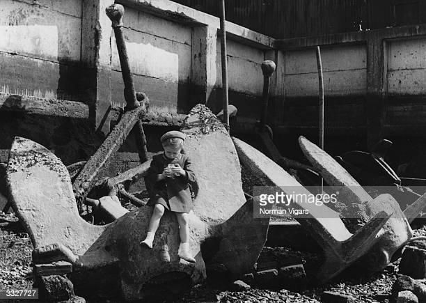 A three yearold child sits on an anchor over four times his size on Southampton's shore