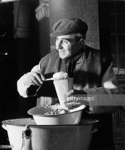 London stall-holder serves a late night customer. The selection on offer includes jellied eels, whelks and winkles. Original Publication: Picture...