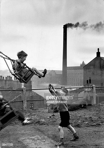 Children play outdoors within sight of the smoke and Yorkshire factories where their fathers work where one day they themselves may find employment...