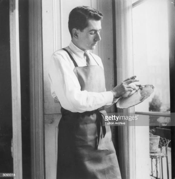 Michael Bentley, a butler, polishing a silver plate.
