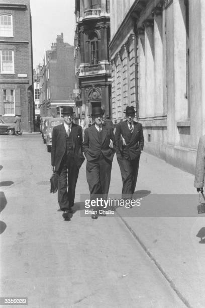Three businessmen sport bowler hats and suits, the traditional uniform in the financial district of London.