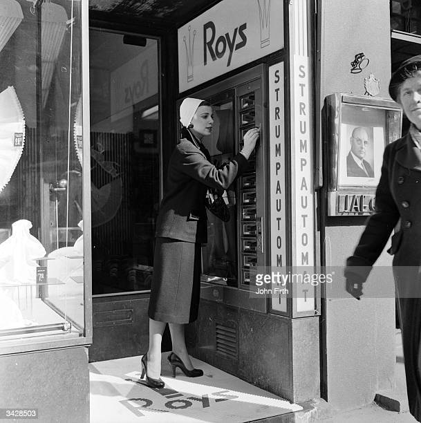 A woman buying a new pair of nylons from a stocking vending machine in Stockholm