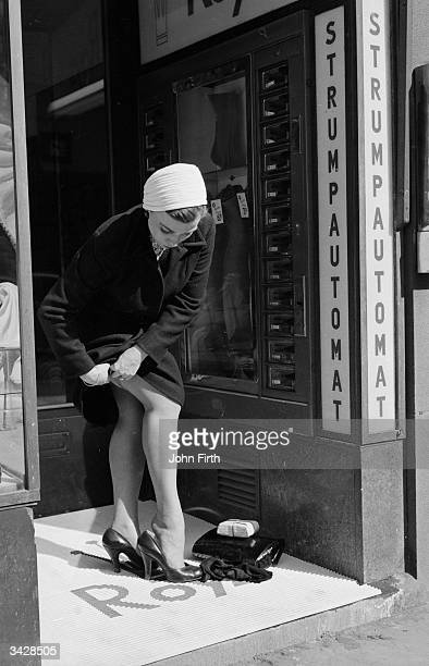 A woman buys a new pair of nylons from a stocking vending machine or automat in Stockholm and changes into them in a doorway