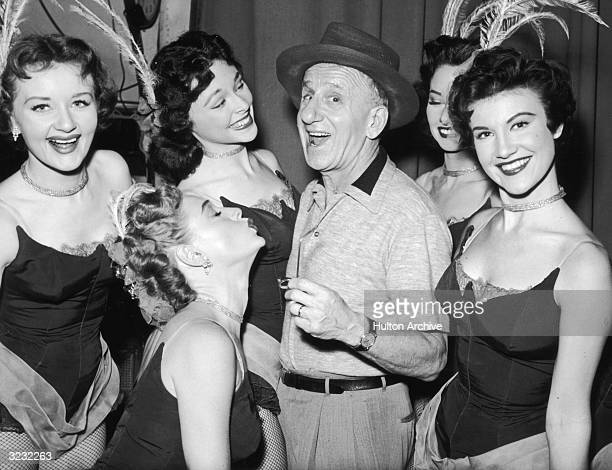 American actor and comedian Jimmy Durante smiling among a group of five dancers in a promotional portrait for the television show 'Texaco Star...