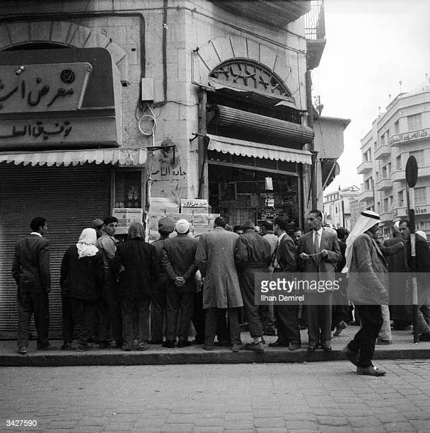 Citizens of Damascus queue to read newspapers on display in the streets